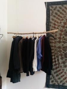 Kleiderstange aus einem Ast und einem Seil an der Decke montiert